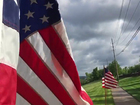 Volunteers place flags along road to honor vets