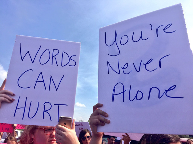 People hold up signs at rally at Smith-Cotton High School